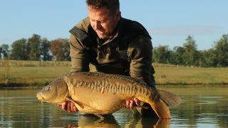 Charlie holds a stunning St Martin's Lake carp for the camera.
